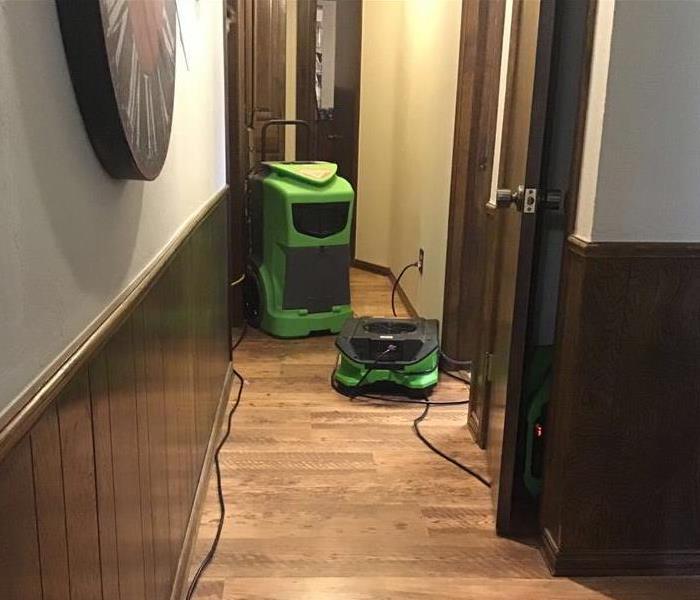 Green air mover and green dehumidifier set up in the hallway of a home.