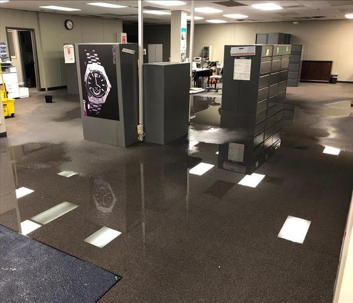 Open office space with big pool of water on the floor after a water loss.