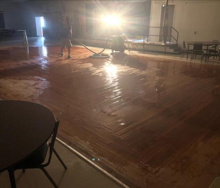 Water damaged wood flooring in a large room.