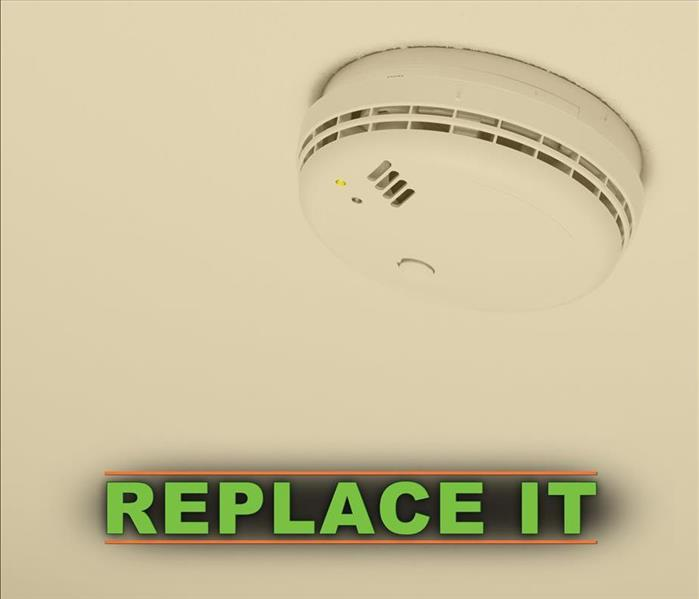 Smoke alarm with the words REPLACE IT